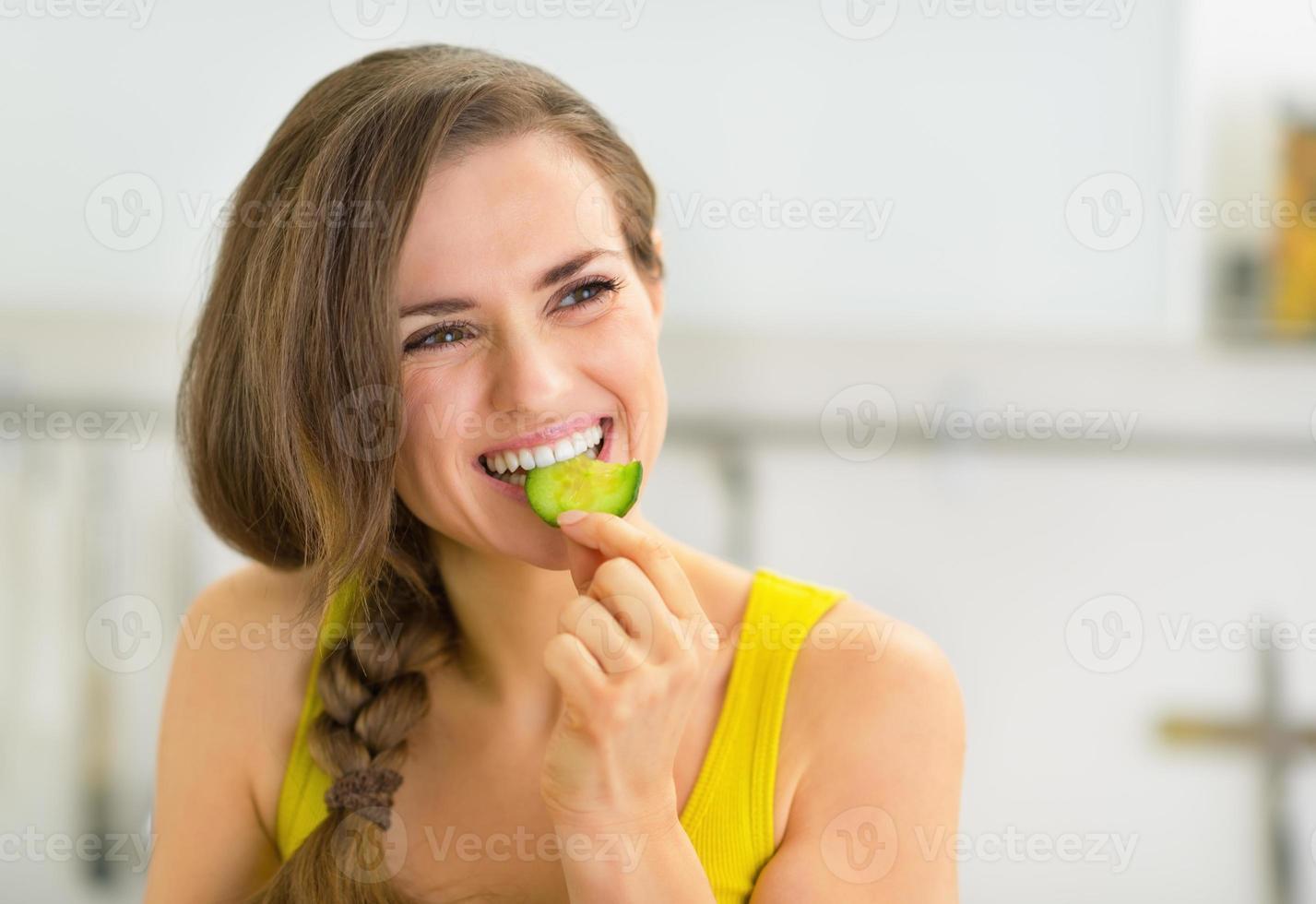 porträtt av ung kvinna som äter gurka i köket foto