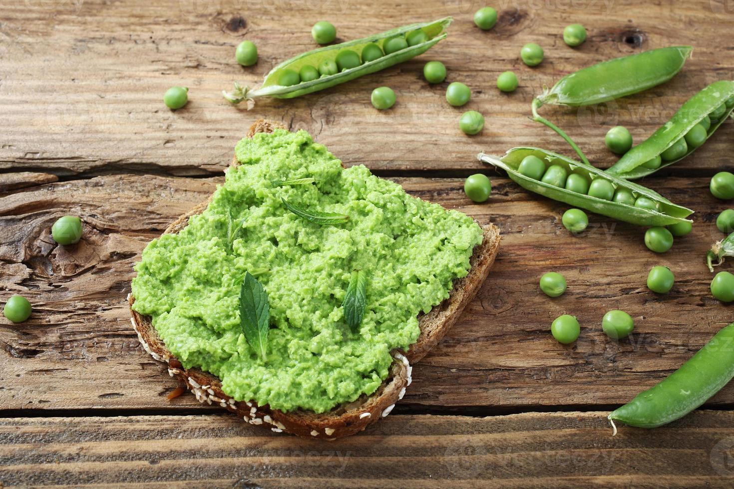 smörgås med gröna ärtor grädde på träbord foto