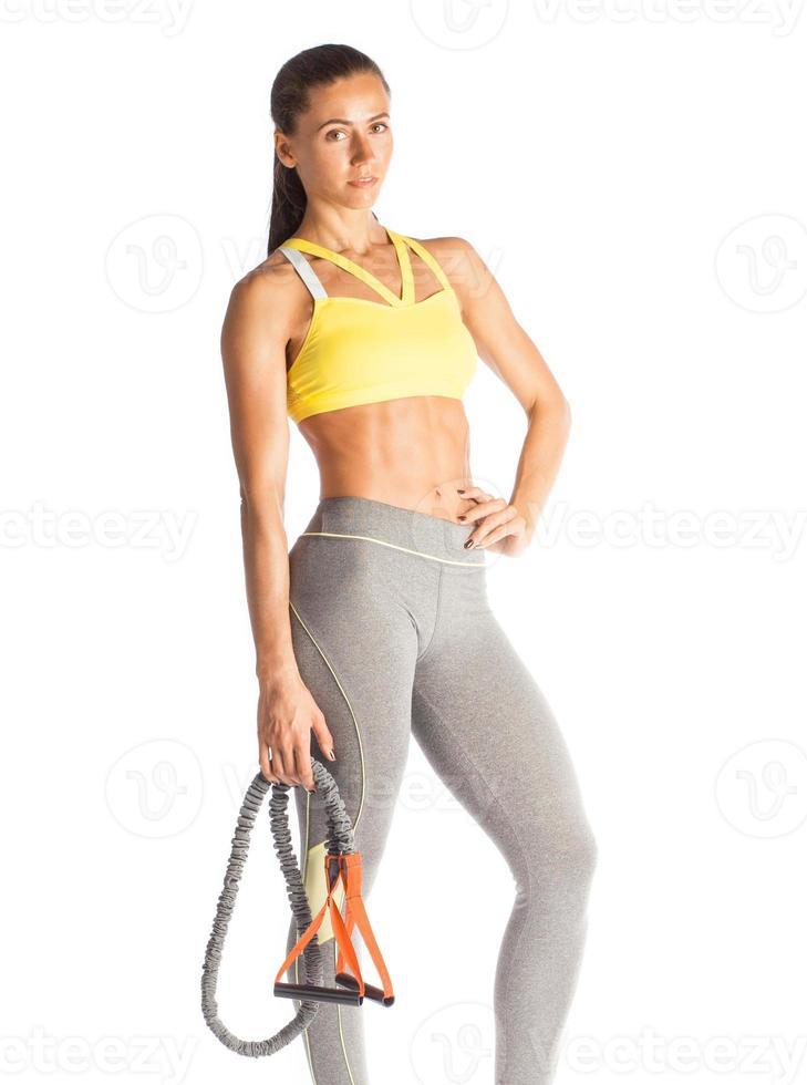 muskulös idrottskvinna stannar med expander isolerad på vit bakgrund foto