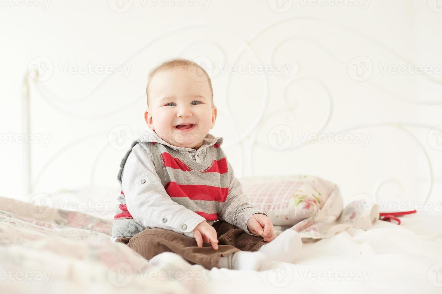 liten pojke spelar i vit studio foto