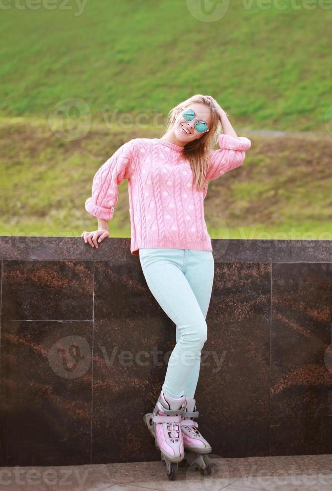ganska snygg kvinna på rullskridskor poserar i staden foto