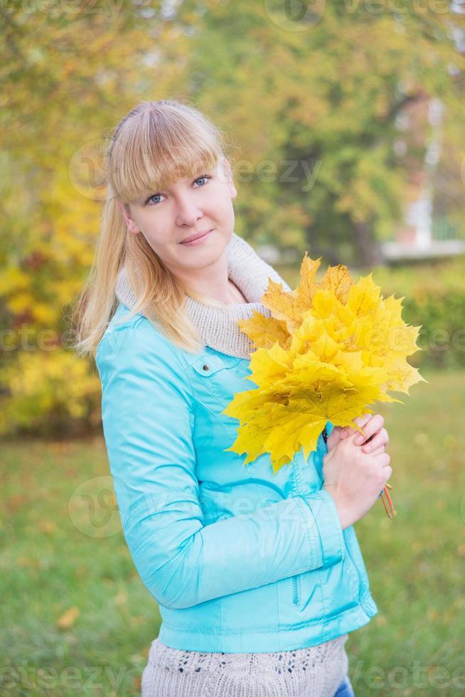blond tjej med gult lönnlöv foto