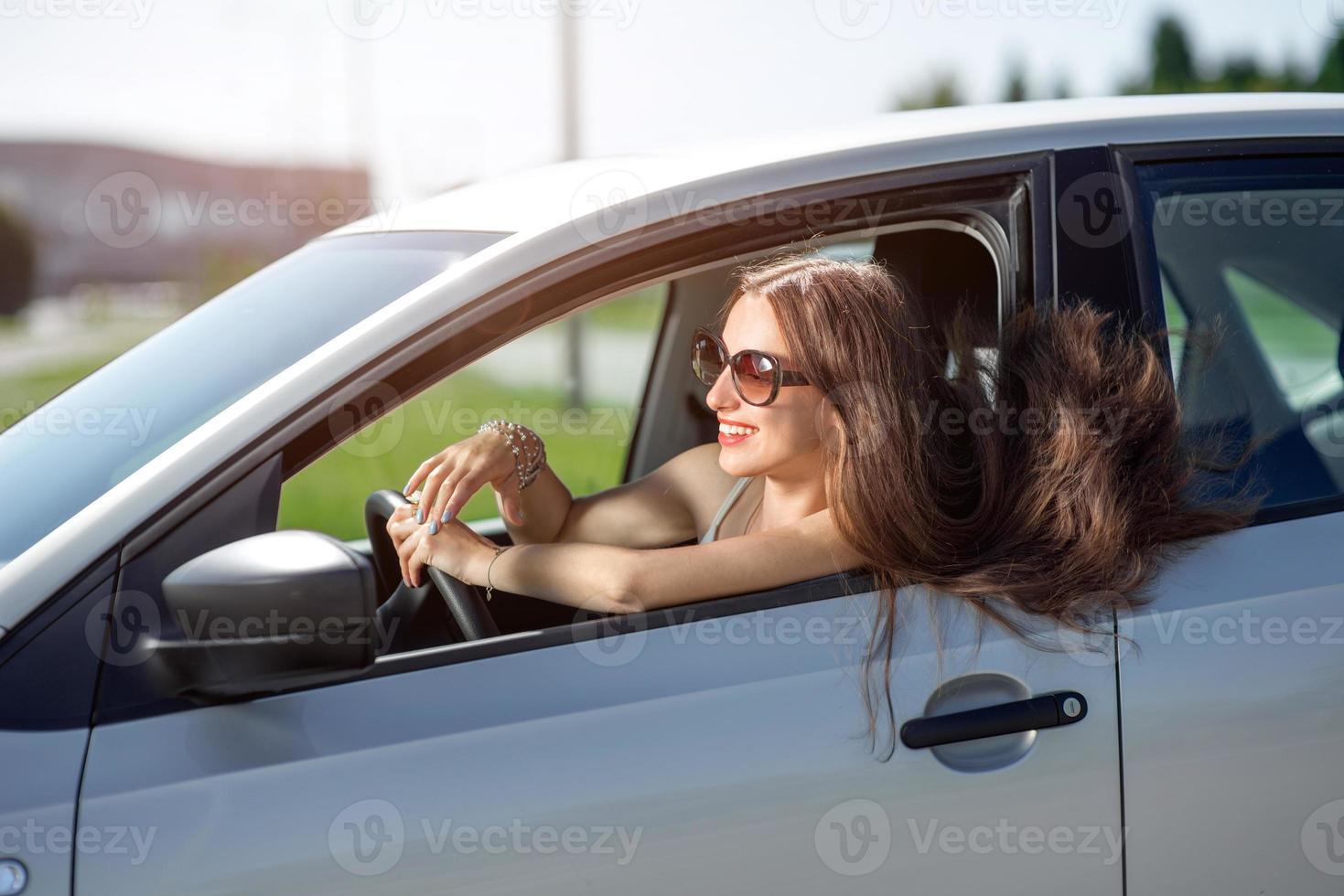 ung leende kvinna som kör sin nya bil foto