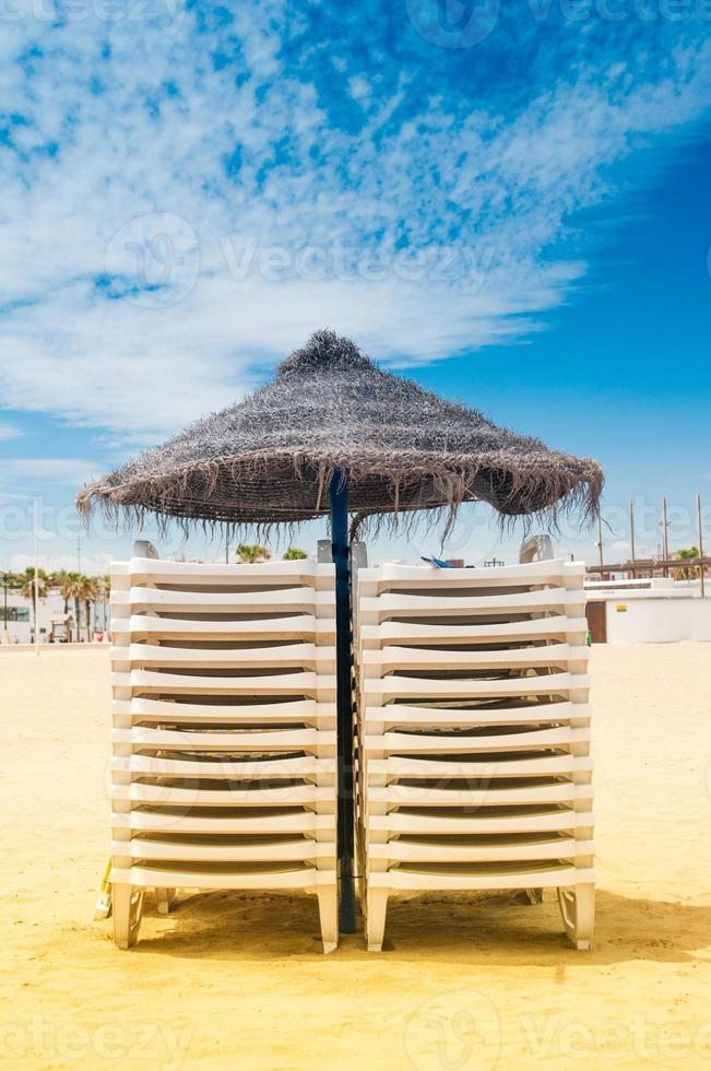 vassparaply och solstolar på stranden foto