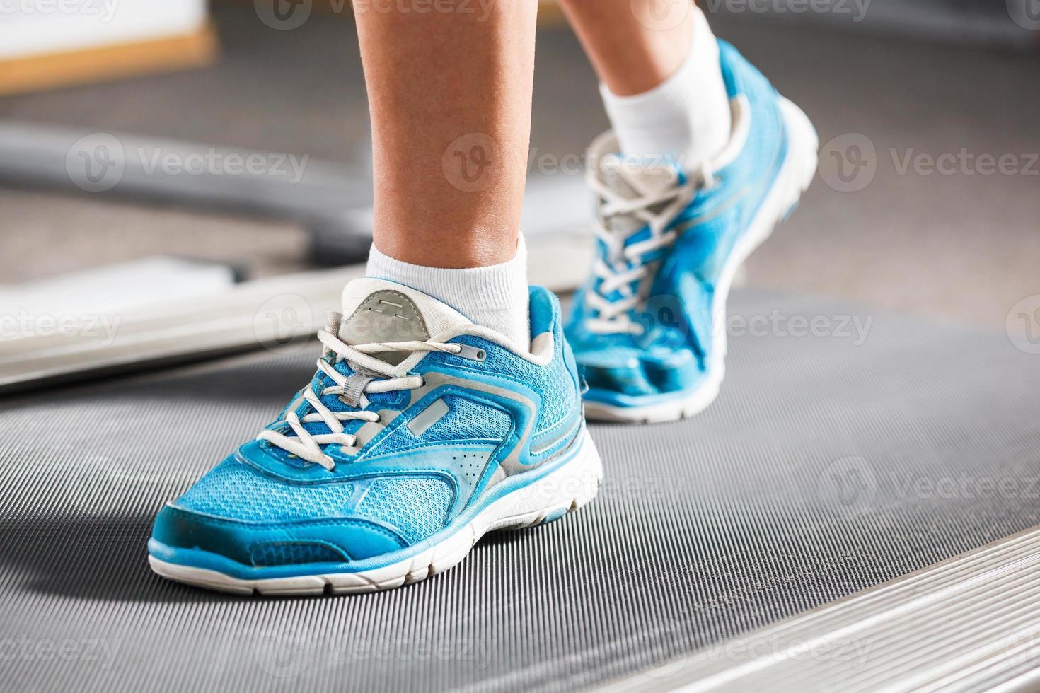 kvinna kör på löpbandet i gymmet. foto