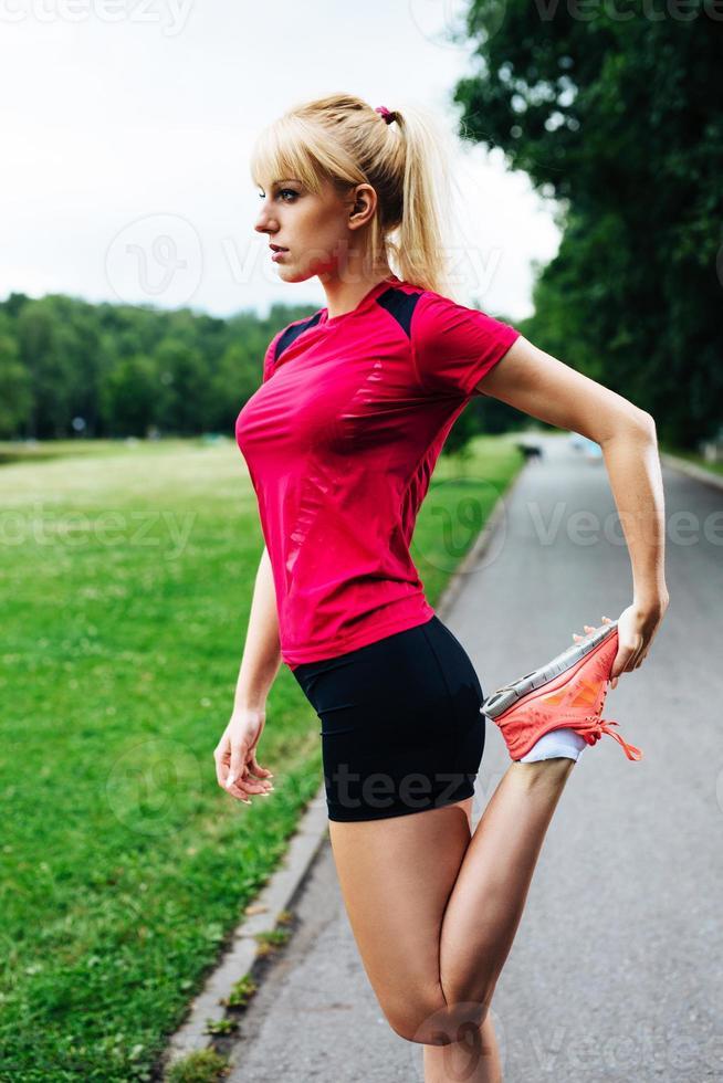 kvinnlig löpare som sträcker sin kropp innan en parkmaraton foto