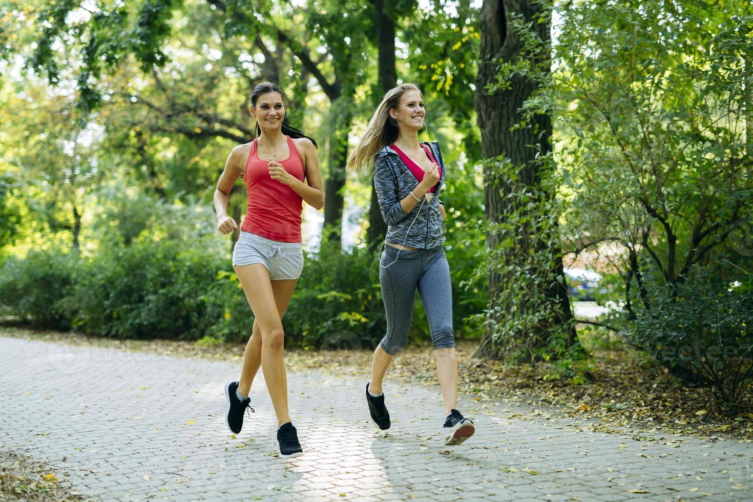 två unga kvinnor som joggar foto