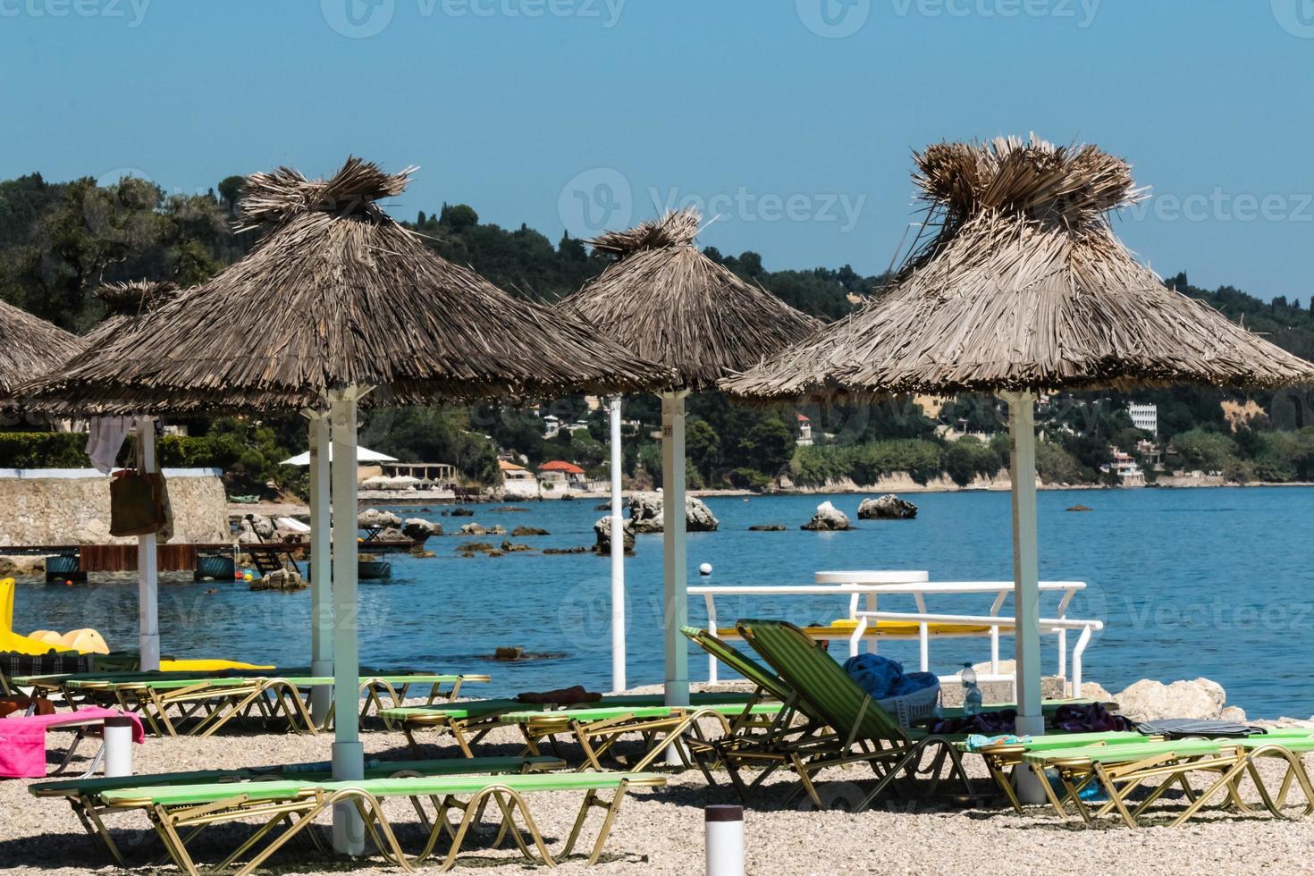 parasoller och solstolar på stranden foto