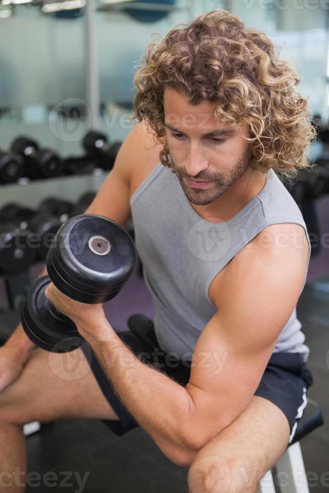 ung man tränar med hantel i gymmet foto