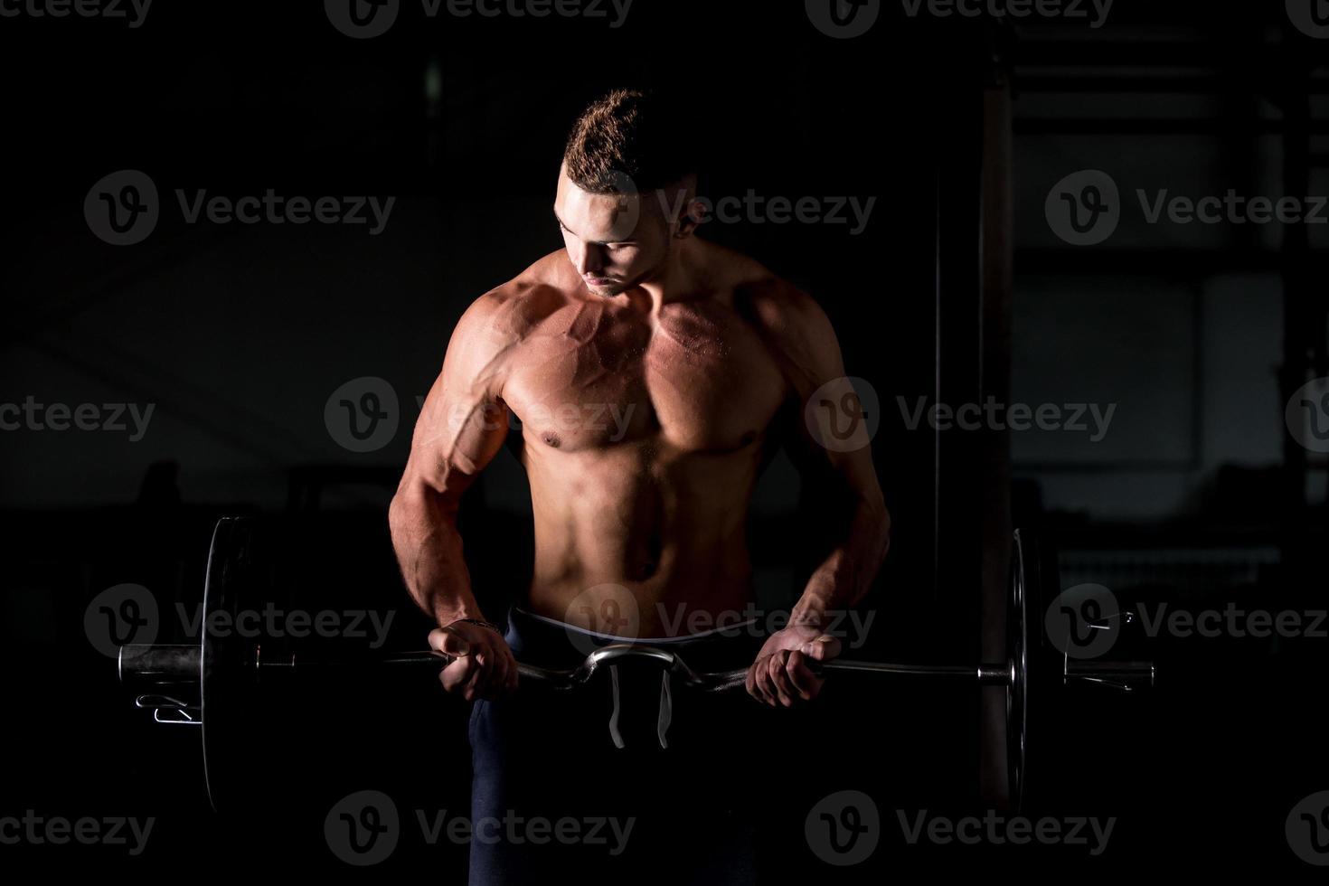 ung man lyfter en skivstång i gymmet foto