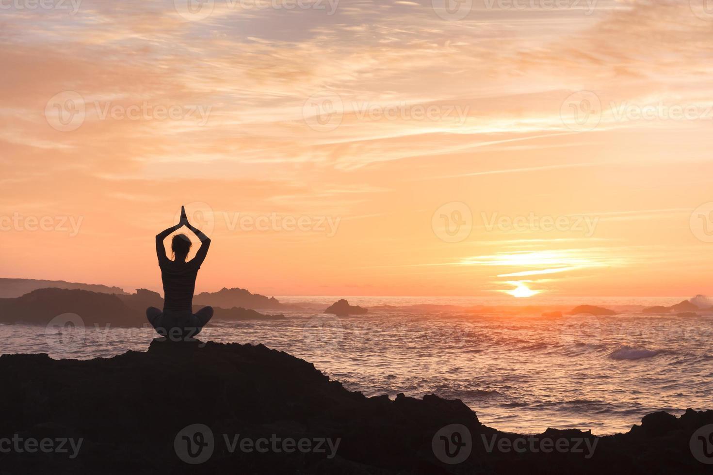 kvinna som bekämpar stress genom att öva yoga nära havet foto