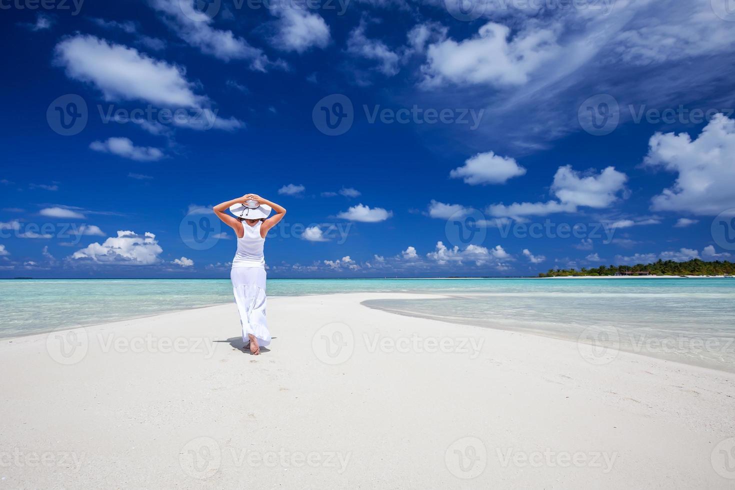 kaukasisk kvinna går längs den vackra kusten foto