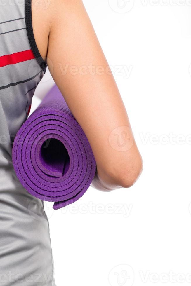 ung kvinna med en yogamatta foto