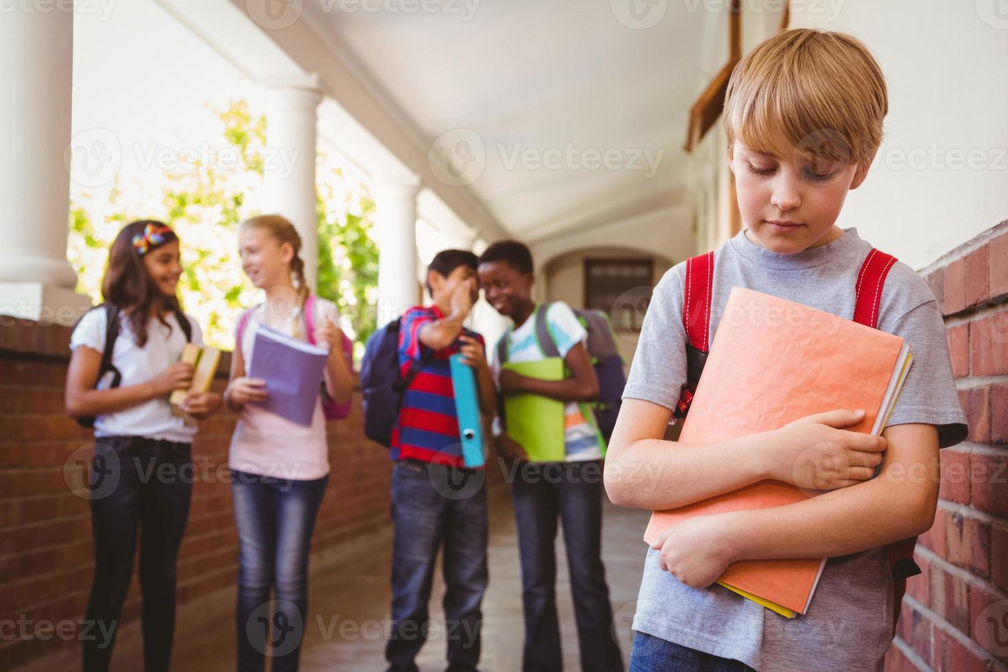 ledsen skolpojke med vänner i bakgrunden på skolans korridor foto