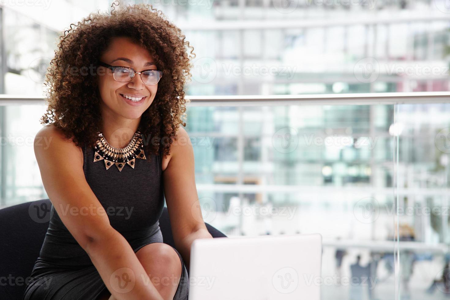 ung affärskvinna som använder bärbar dator, ser till kameran foto