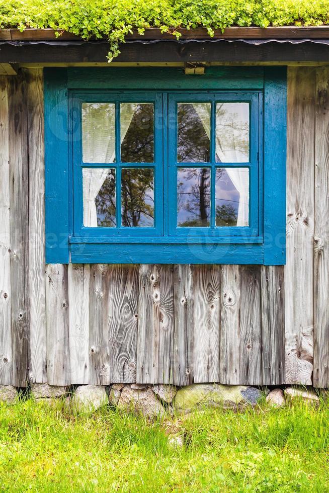 forntida svenskt trägård med blått fönster foto