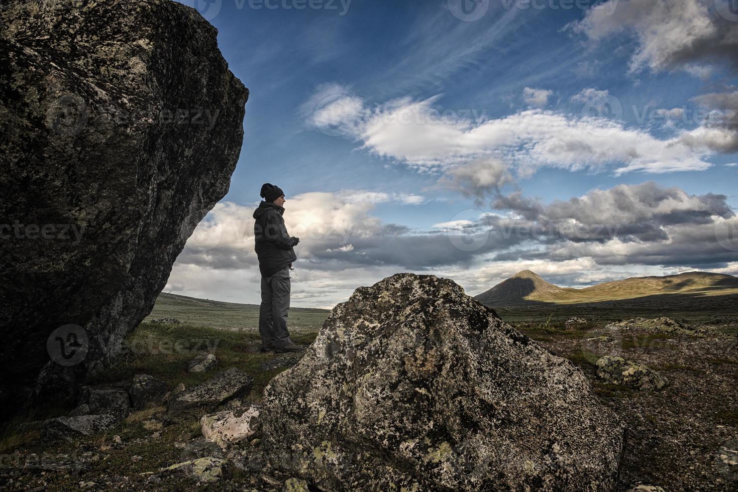 vandrare och stenblock som tittar på vildmarken foto