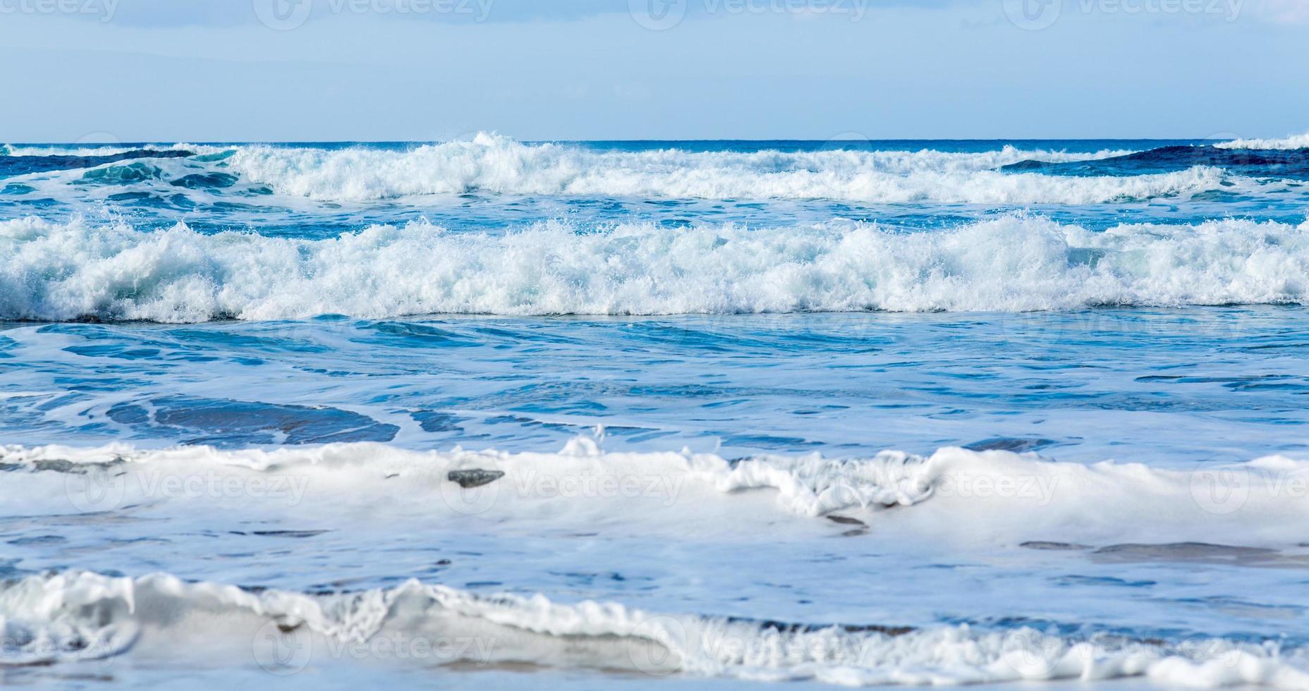 rader med vågor som kommer till stranden foto