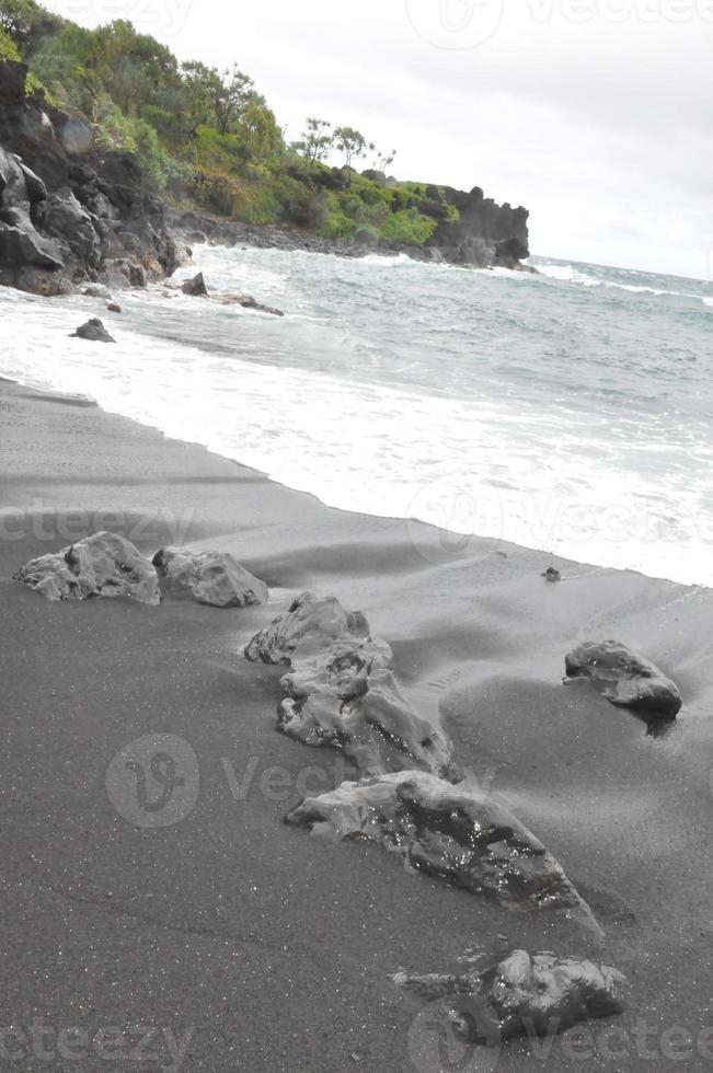 svart sandstrand vid waianapanapa delstatspark i maui, hawaii foto