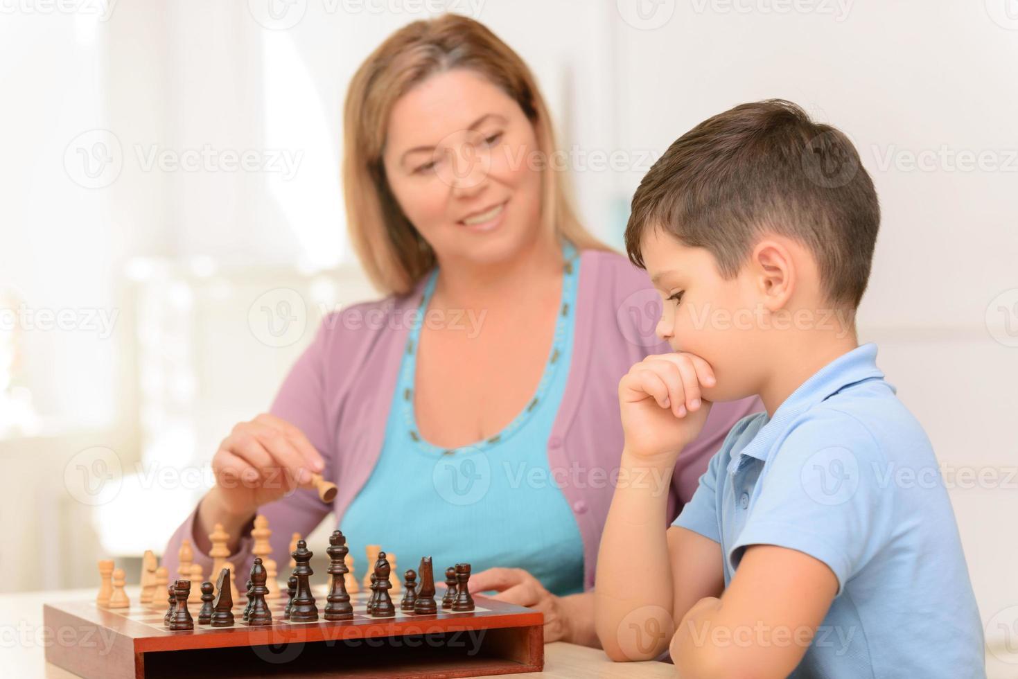mormor sitter vid bordet med pojken foto