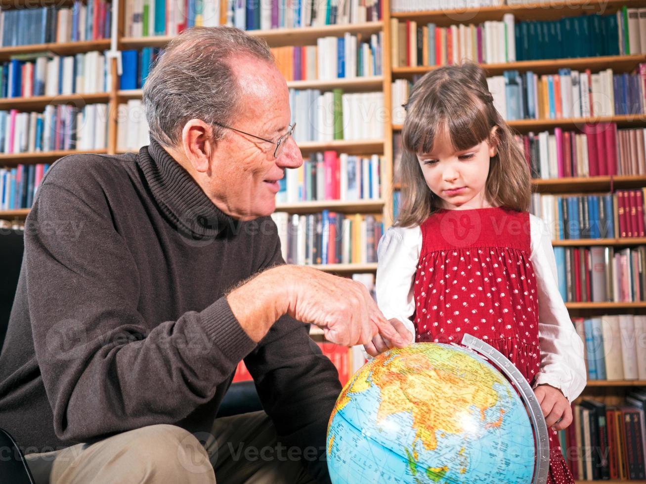 äldre och barnbarn tittar på ett jordklot foto