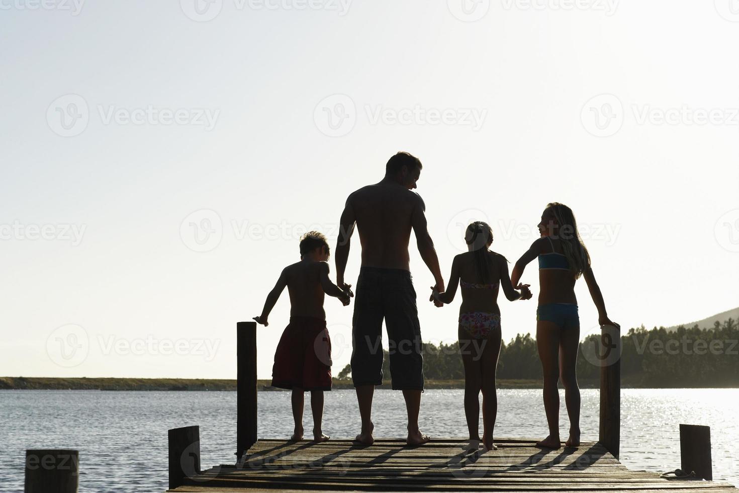 familj som står på kanten av bryggan foto