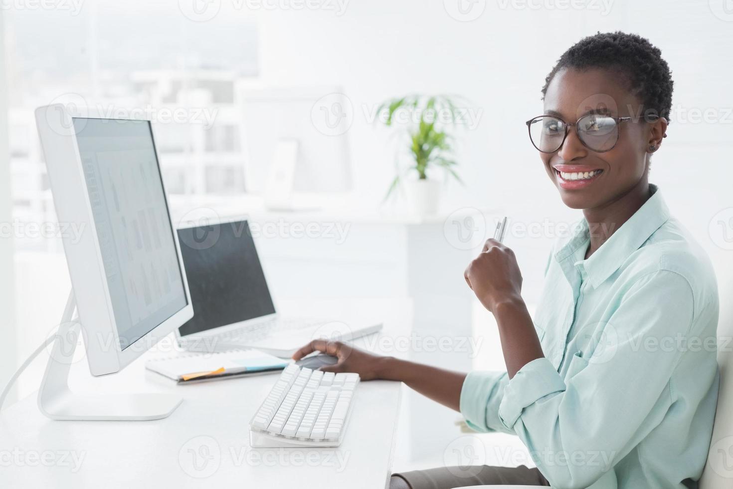 glad affärskvinna som arbetar vid skrivbordet foto