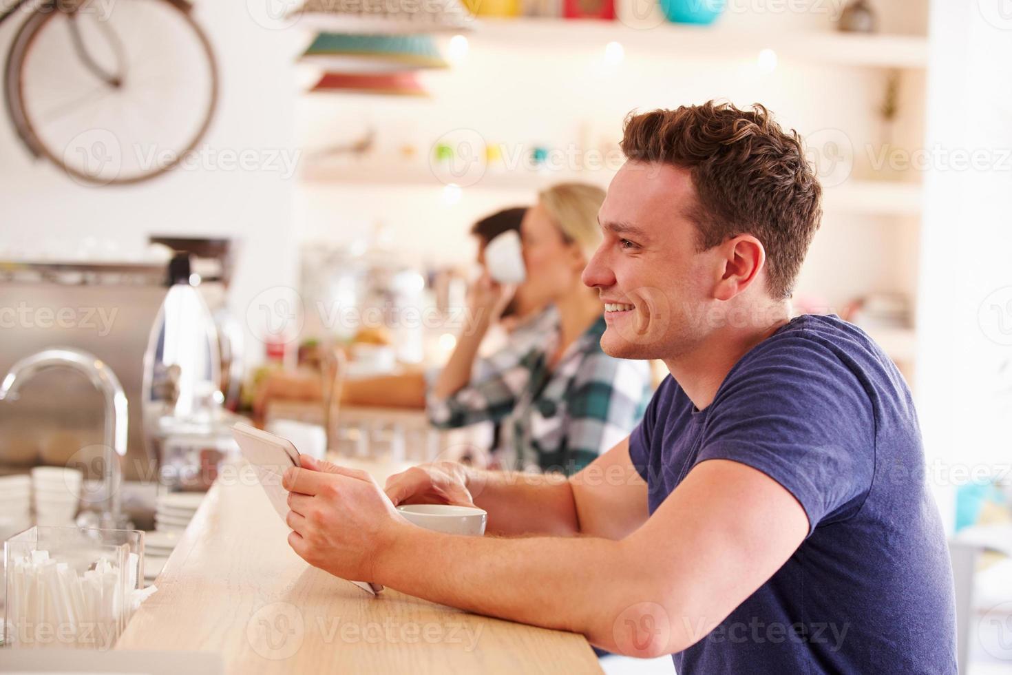 ung man använder surfplatta på ett café foto