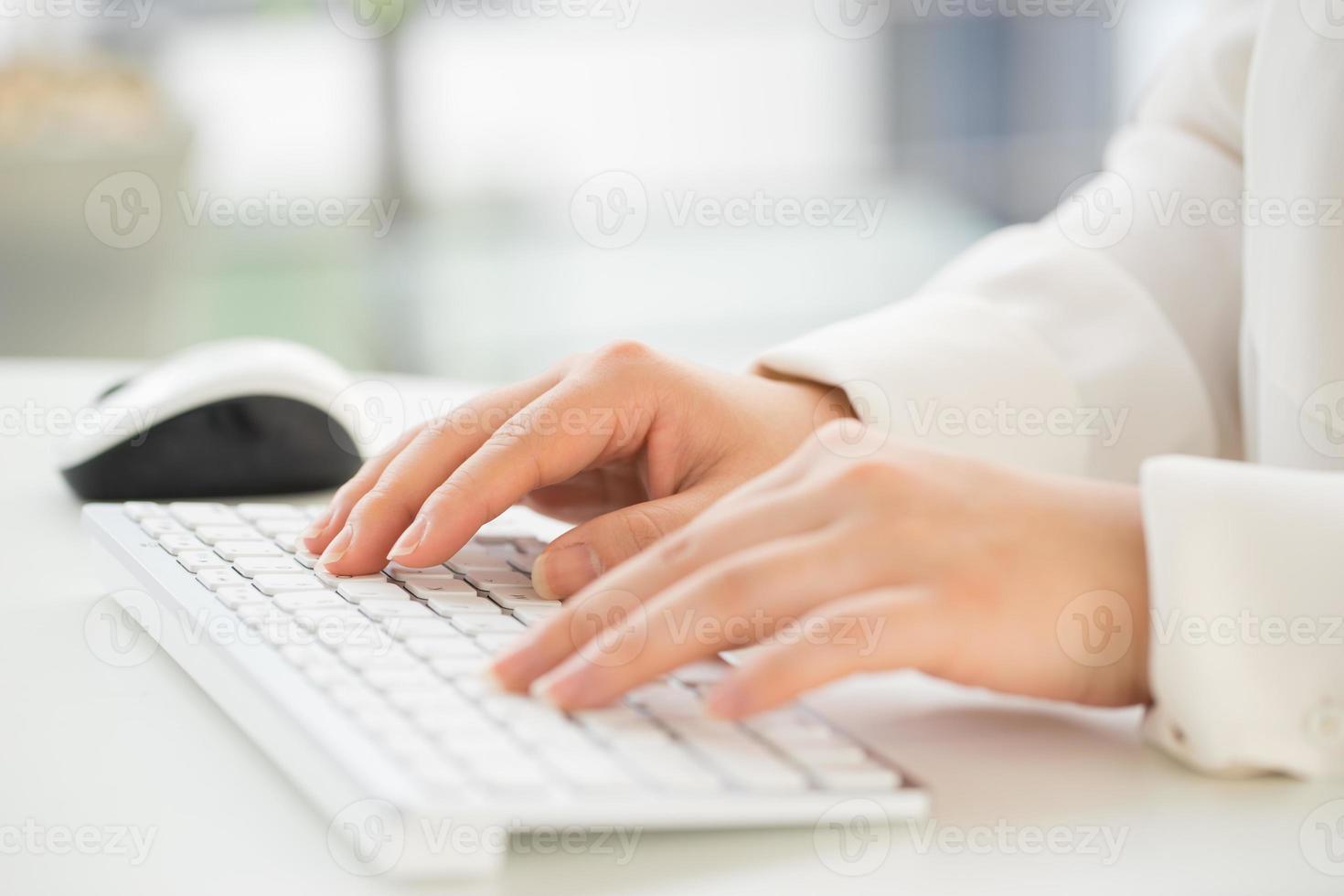 händerna på ett kontor kvinna att skriva tangentbordet med kreditkort foto