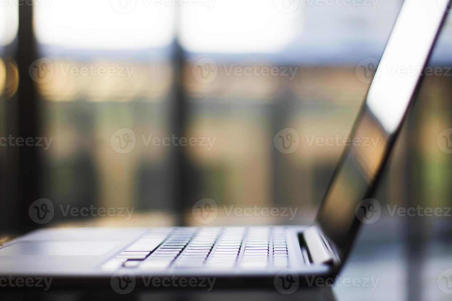 modern bärbar dator på glasbord vid solnedgången foto