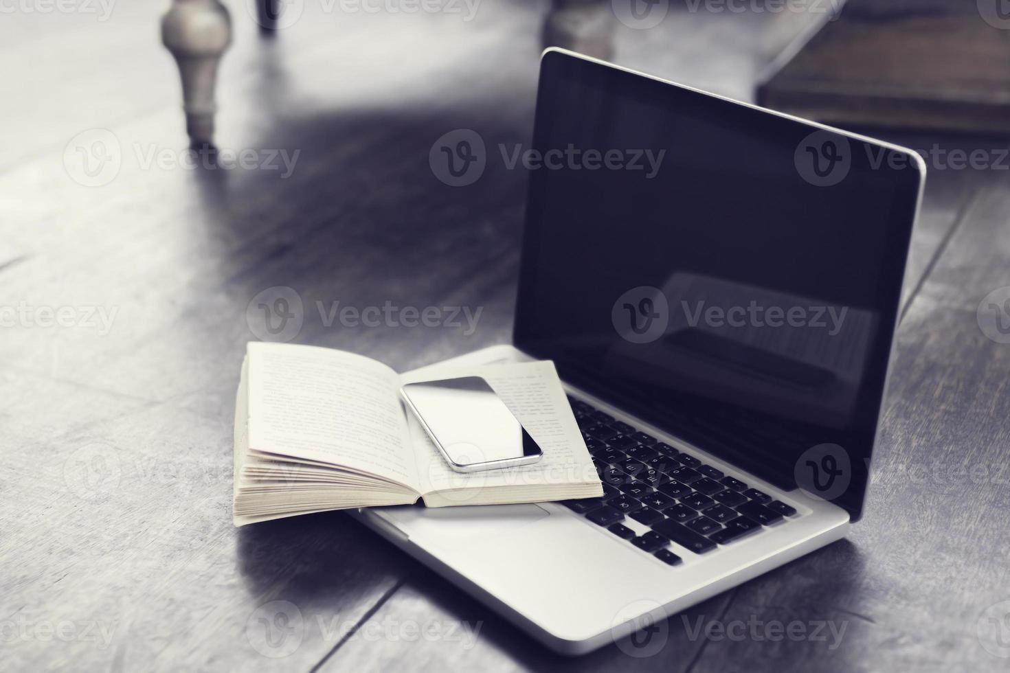 mobiltelefon med öppen bok och bärbar dator på golvet foto