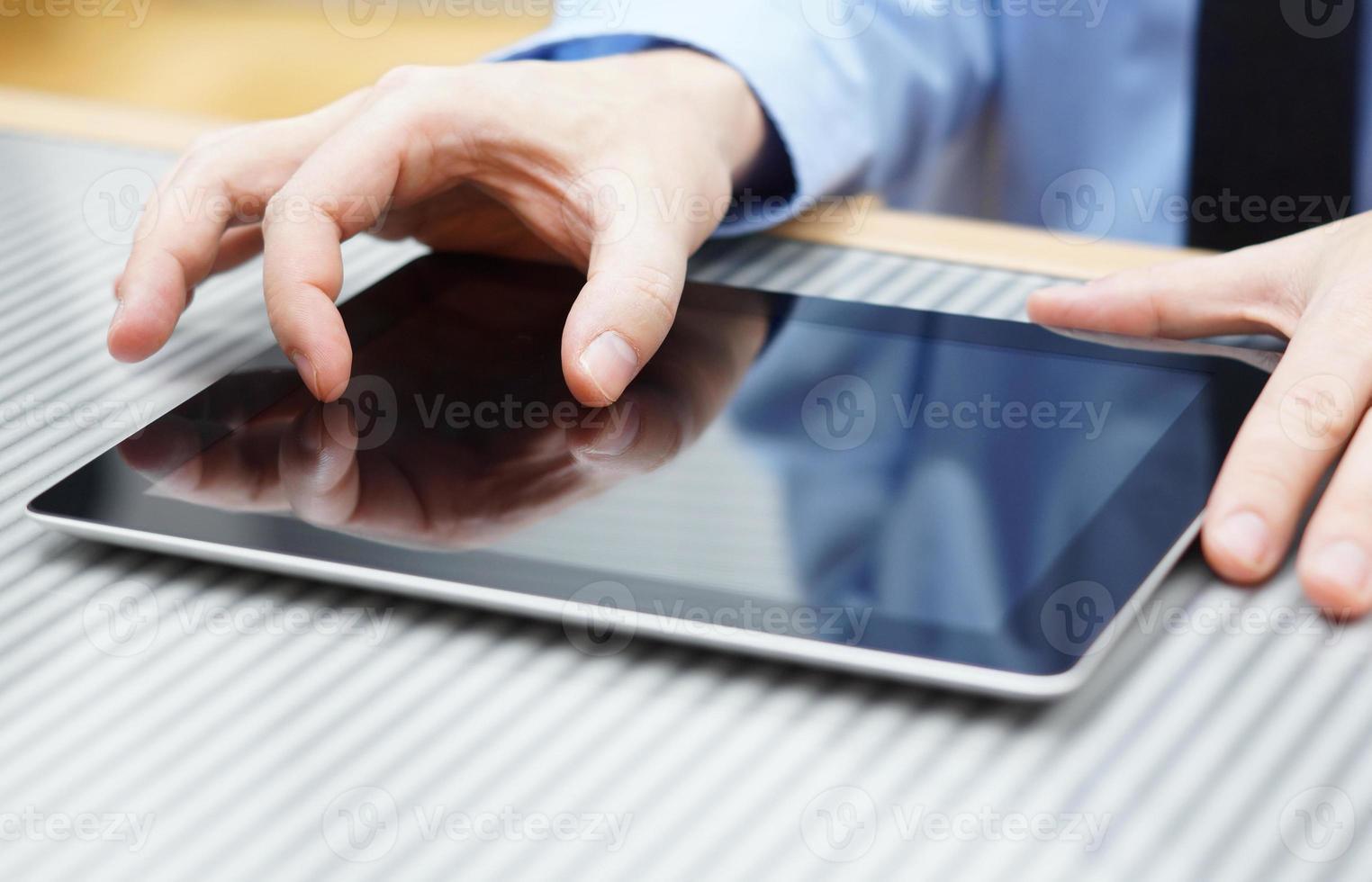 affärsman som flyttar två fingrar på pekskärmen på surfplatta foto