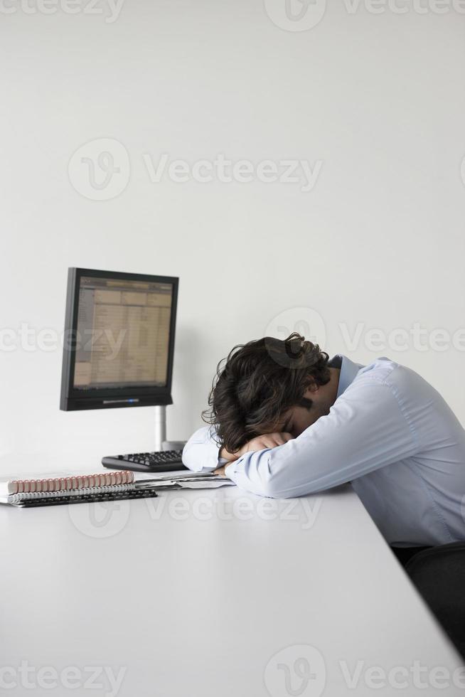 affärsman som vilar på kontorsskrivbordet foto
