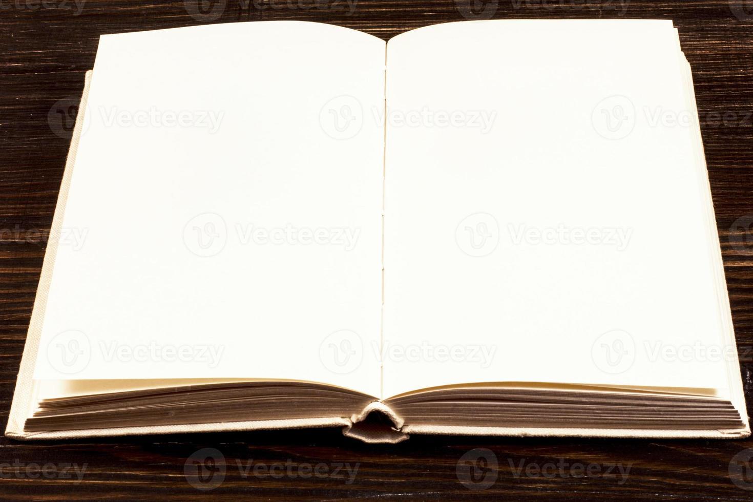 öppen bok på träskrivbord. foto