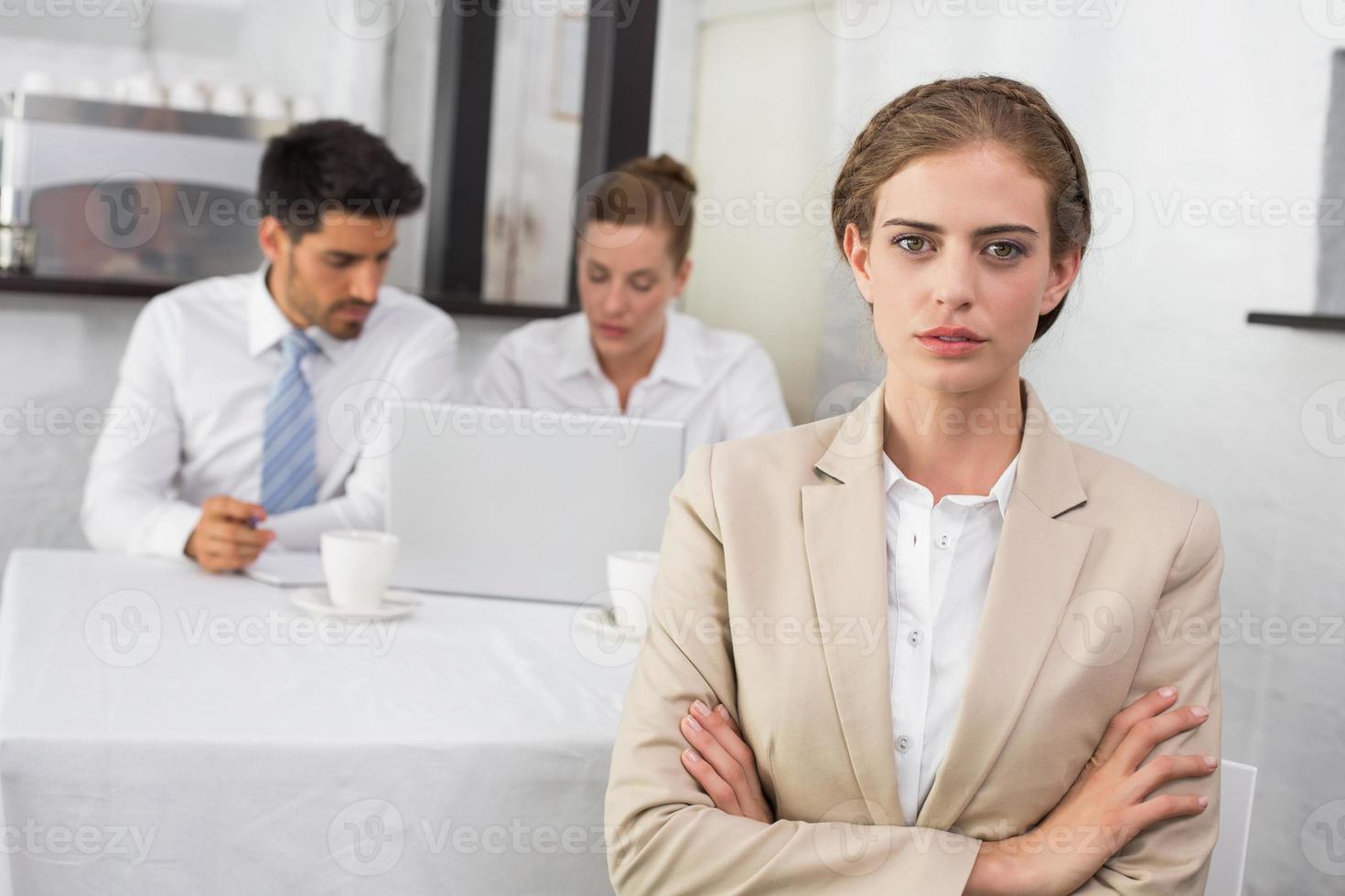 säker affärskvinna med kollegor på kontorsskrivbord foto
