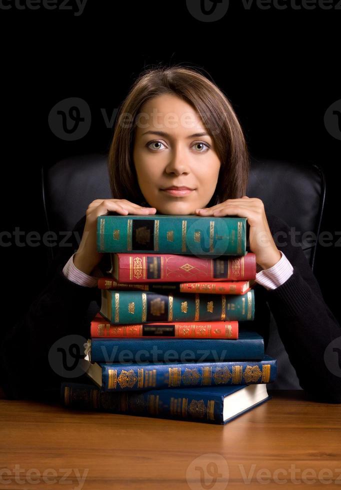 ung kvinna med många bok vid skrivbordet foto