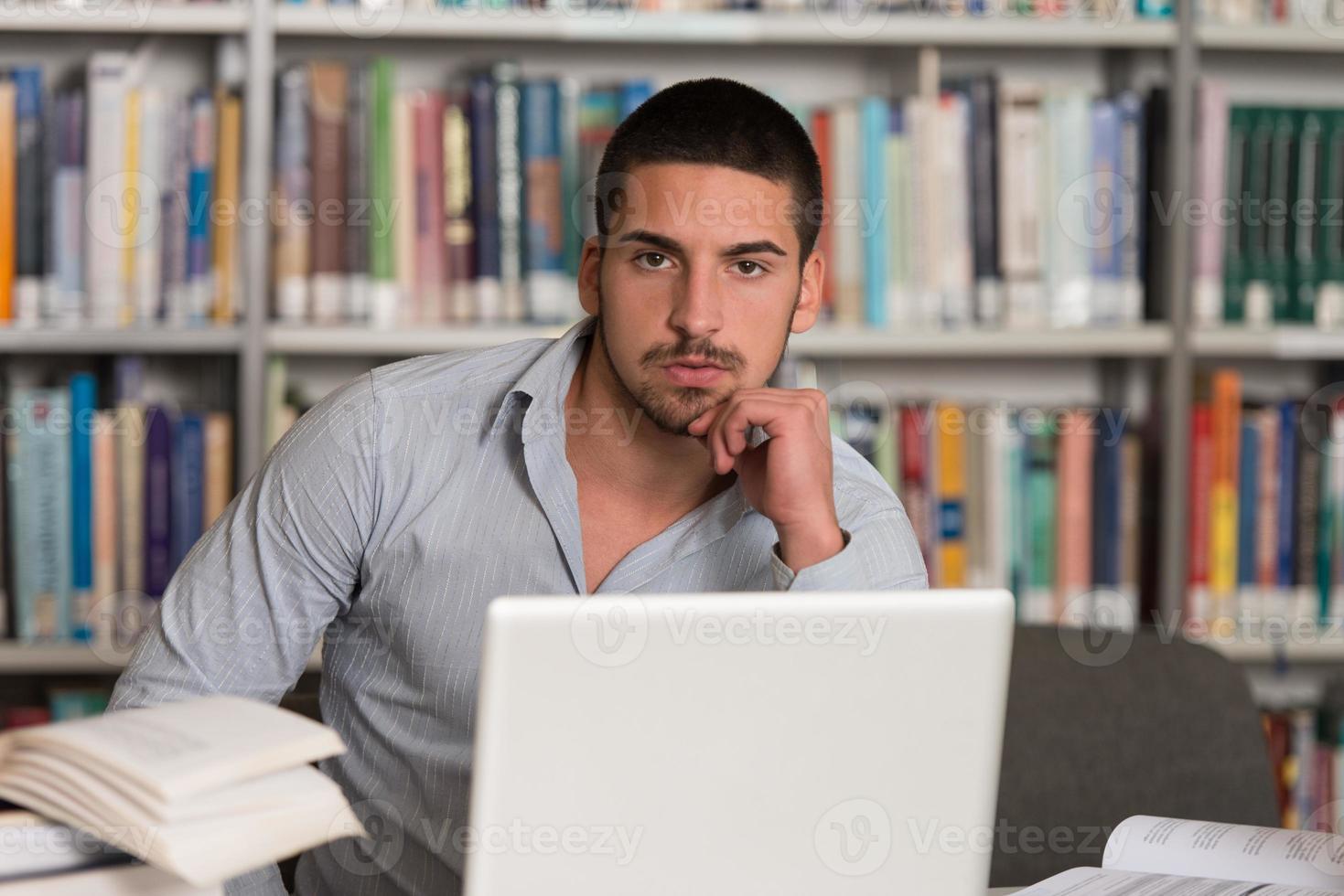 stressad student som gör sina läxor vid skrivbordet foto