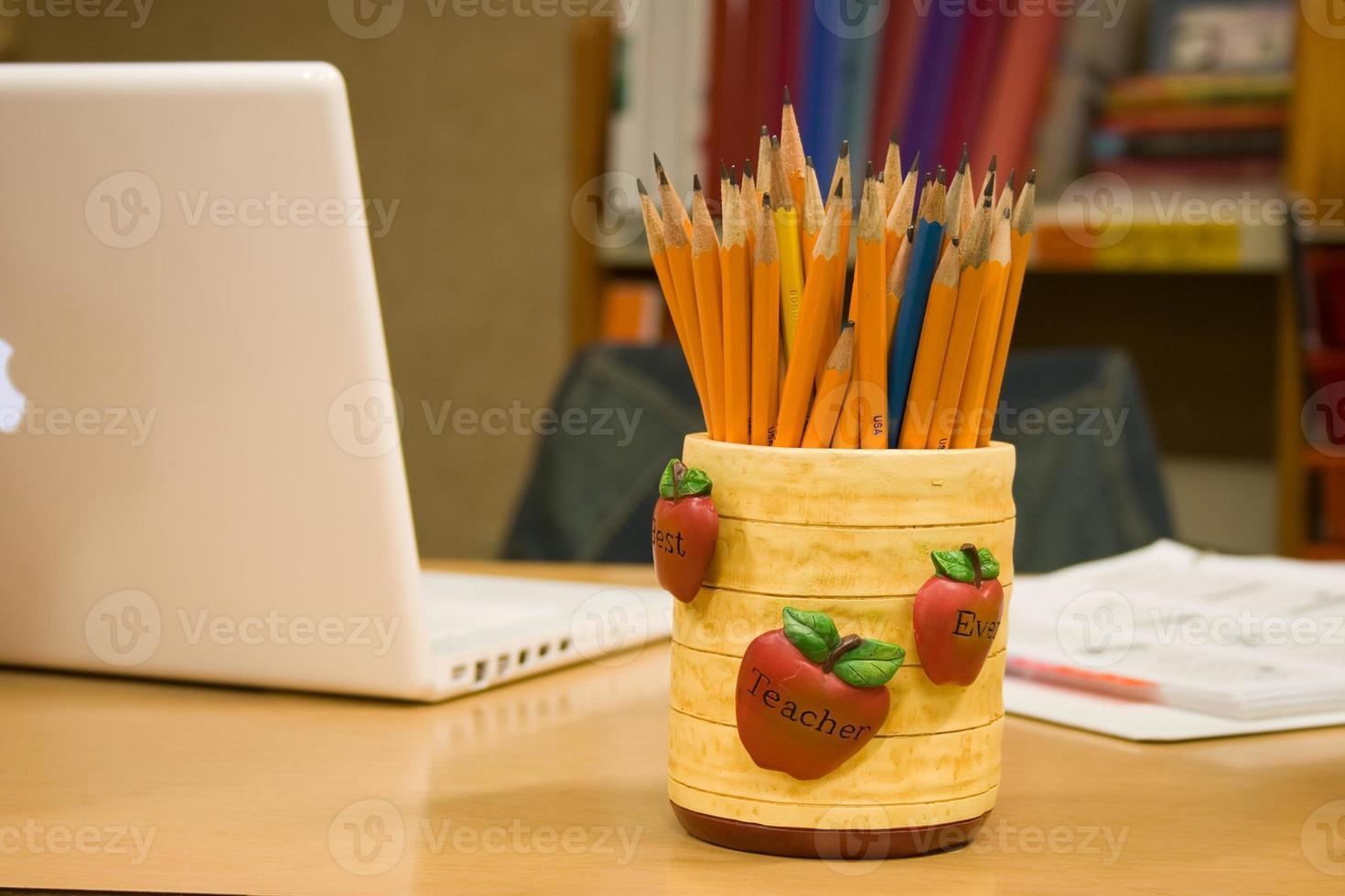 lärares skrivbord med laptop och pennor foto