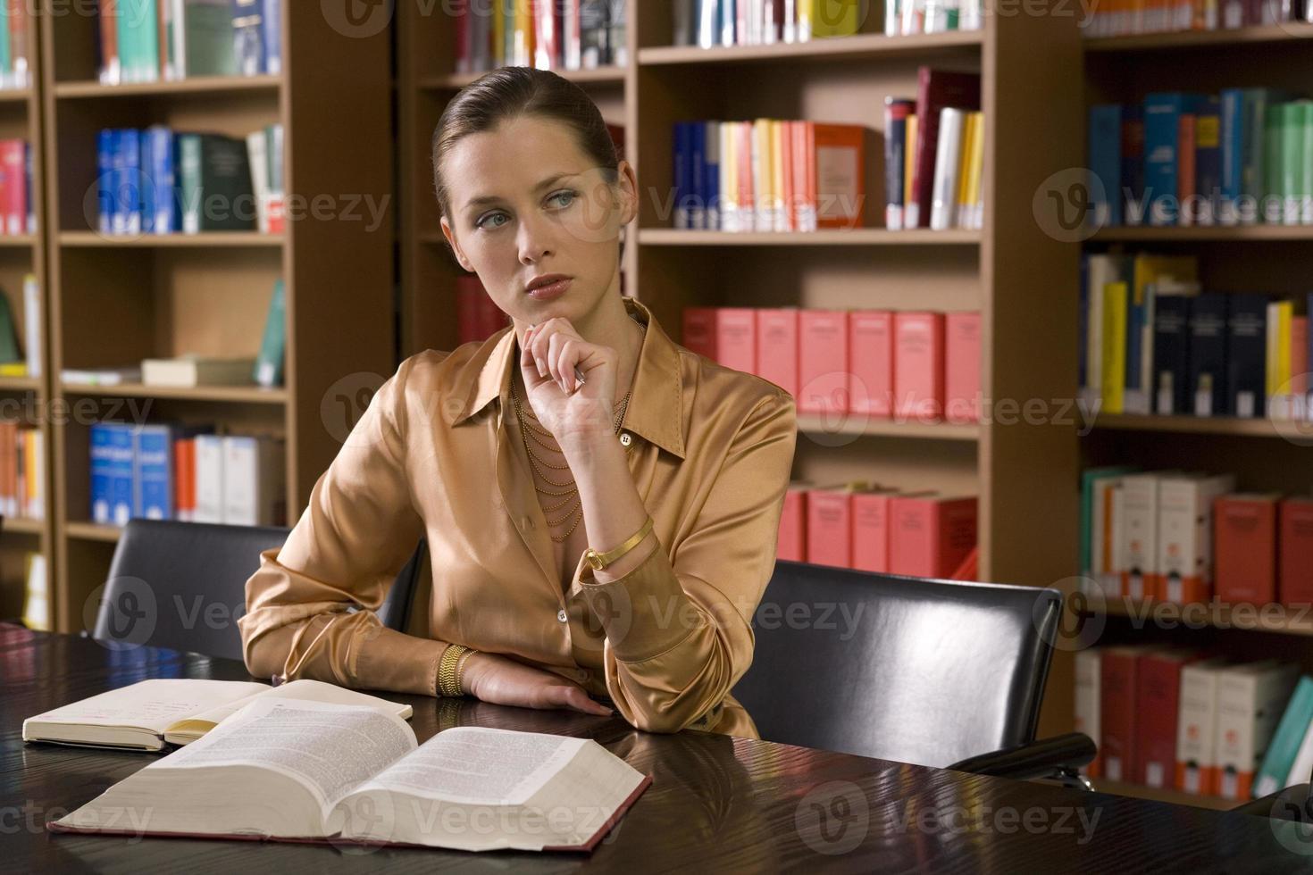 kvinna med boken vid skrivbordet i biblioteket foto