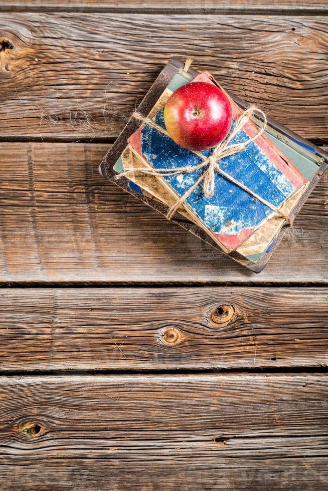 gamla böcker och äpple på skolskrivbordet foto