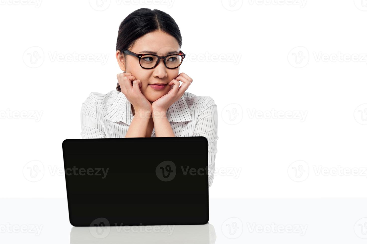 affärskvinna vid sitt skrivbord, tittar bort foto