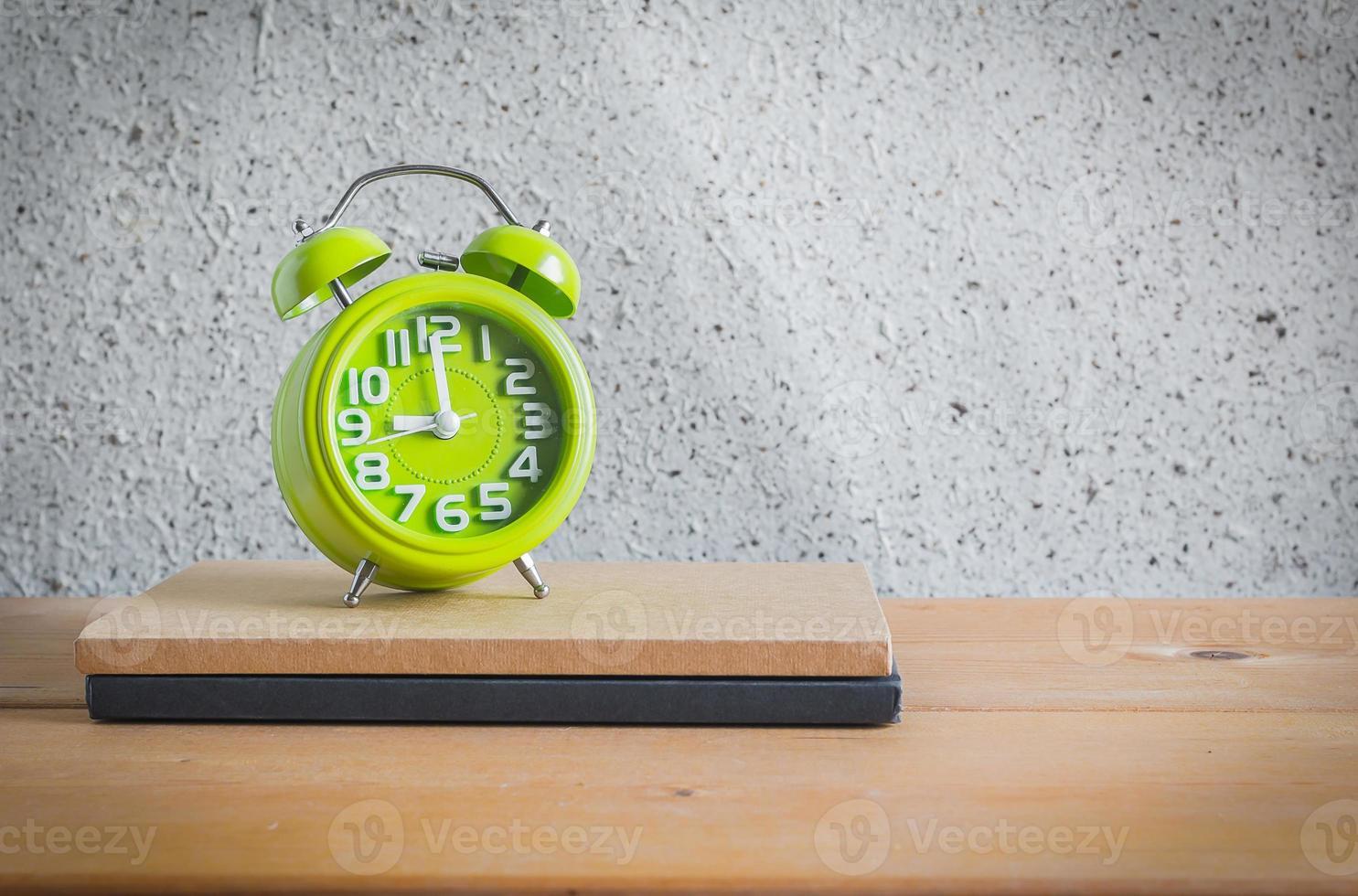 klocka och anteckningsbok på träbord, stilleben foto