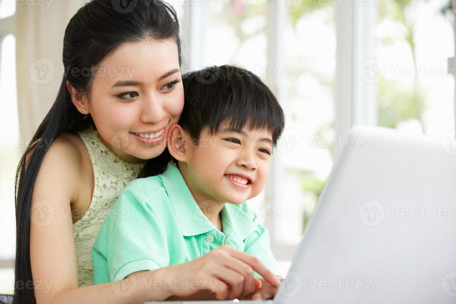 mamma och son sitter vid skrivbordet på bärbar dator foto
