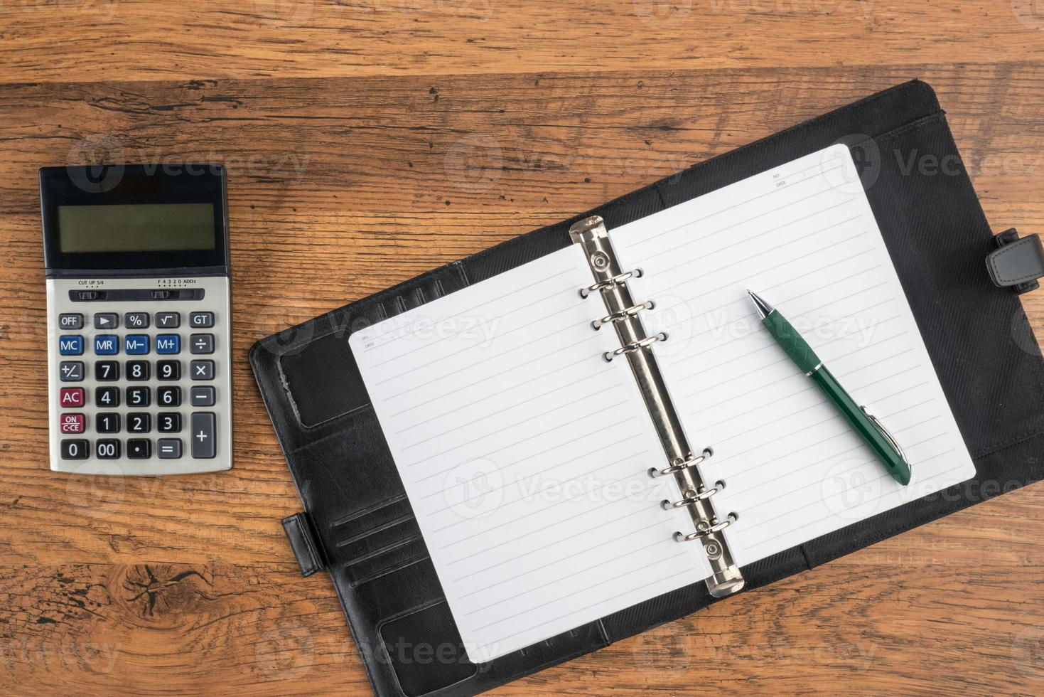 anteckningsbok och penna med miniräknare på skrivbordet foto