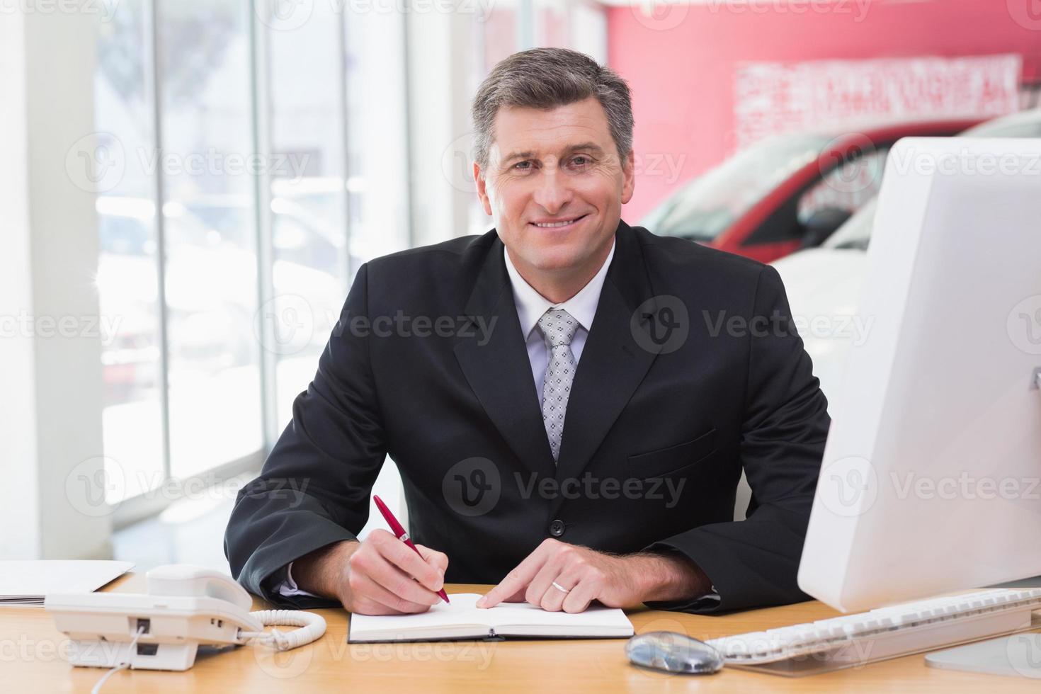 le affärsman som skriver på Urklipp vid sitt skrivbord foto
