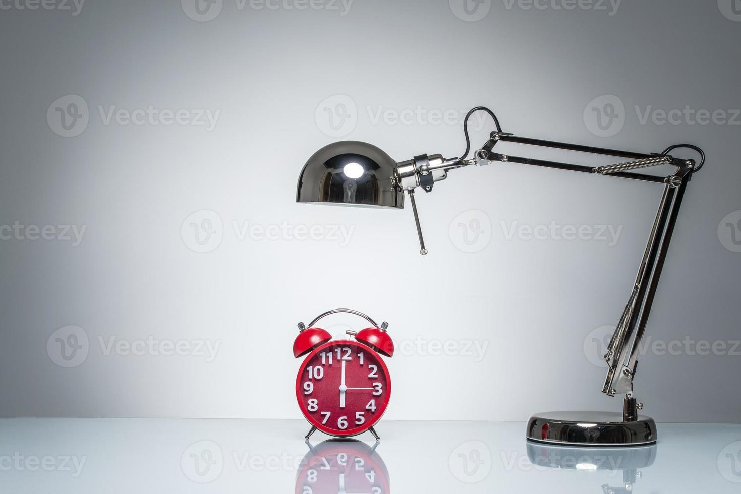 lyser upp röd väckarklocka med skrivbordslampa foto