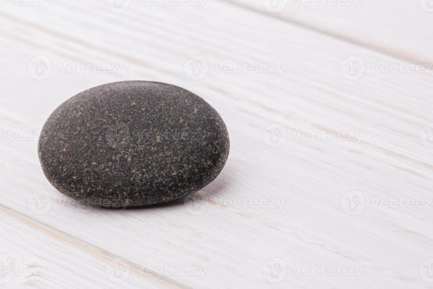 sten på ett träbord foto