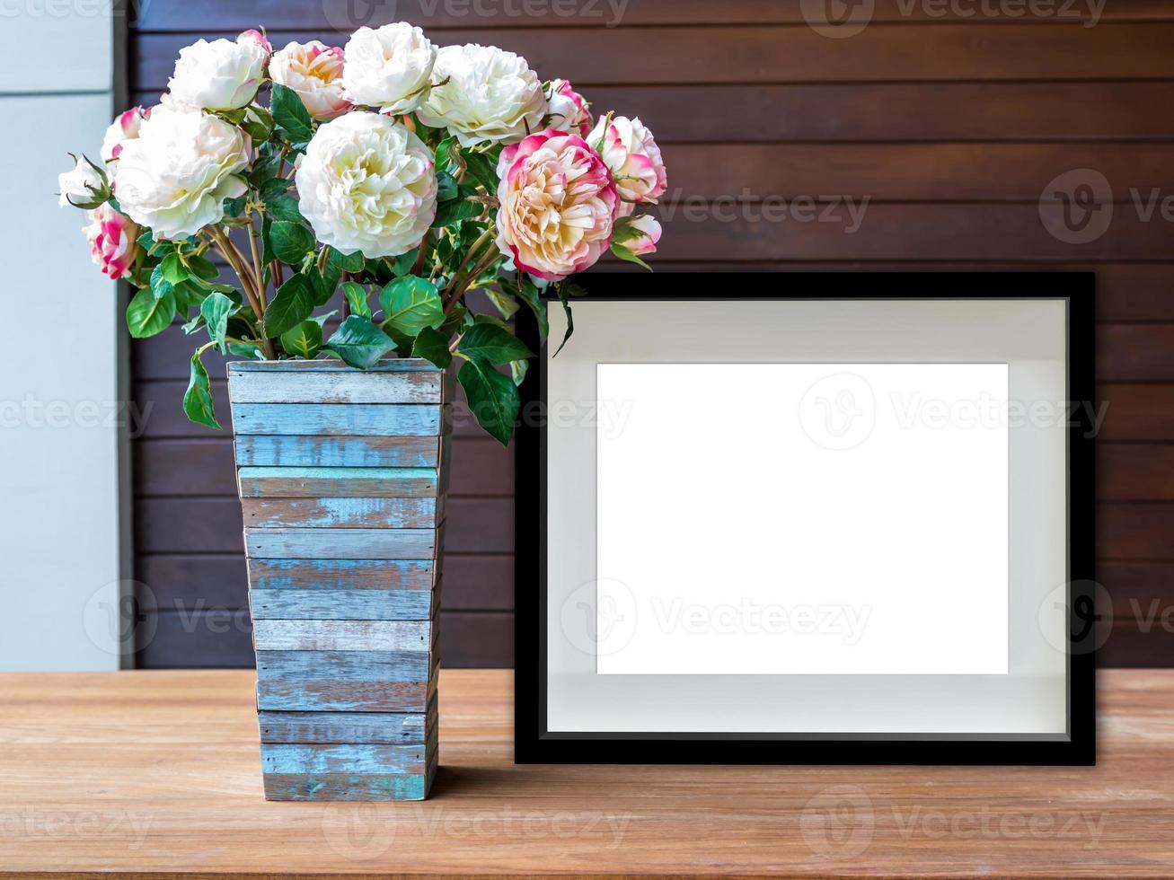 blank svart bildram och blommor vas på trä skrivbord foto