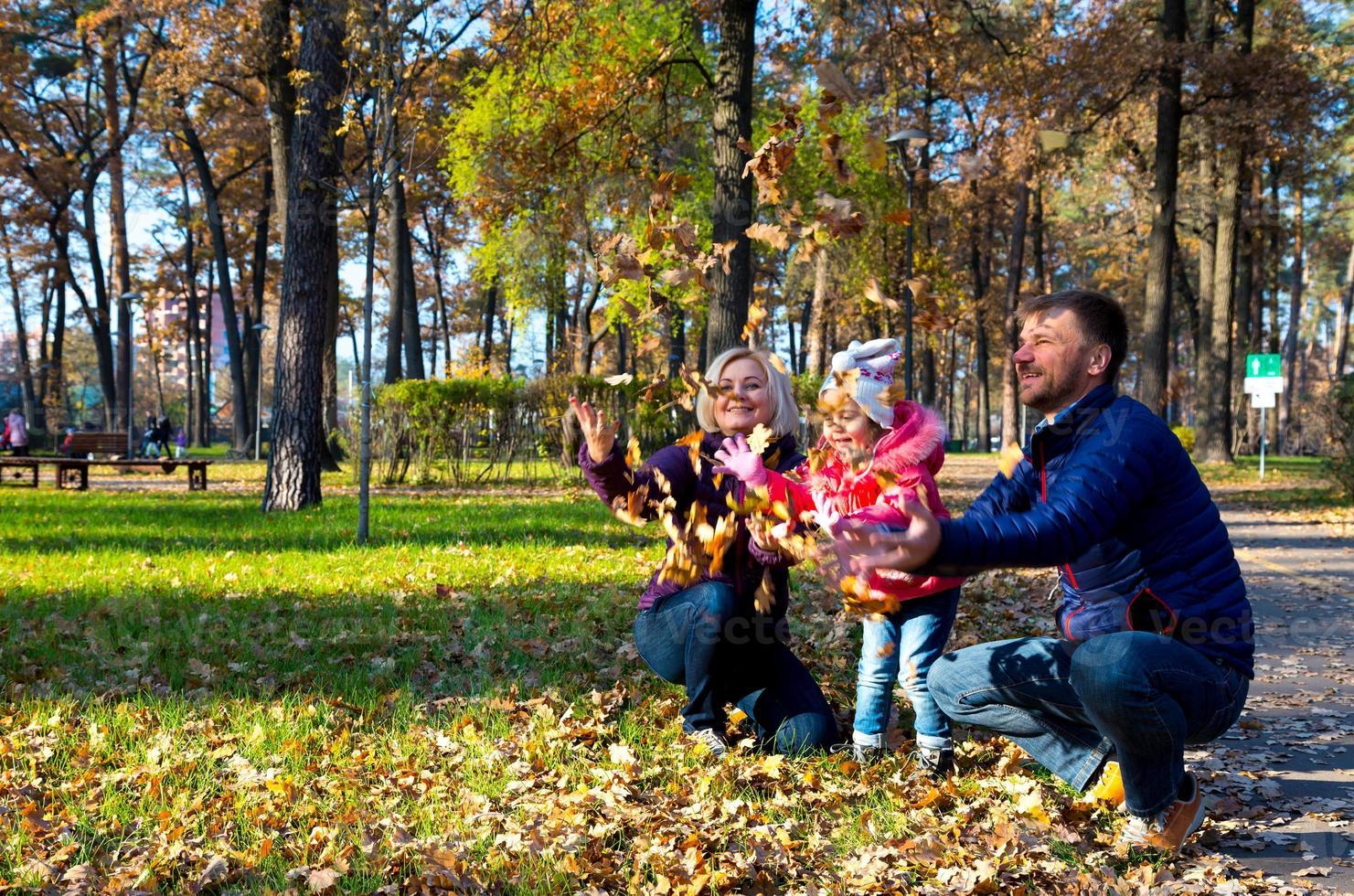 sorglös europeisk familj som leker i höstlig park foto