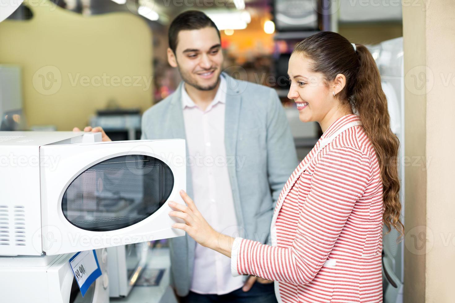 lyckligt familjpar som väljer ny mikrovågsugn foto